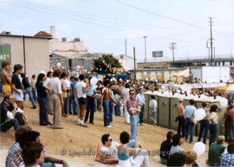 1982 - San Diego Lambda Pride Festival, Crowd of people sitting and standing on dirt slope.