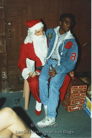 P001.289m.r.t X-mas: a man with a hoodie jean jacket sitting on Santa's lap