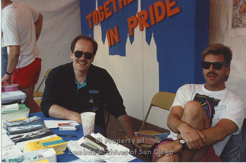 P001.062m.r Pride 1991: 2 people in the AIDS Foundation San Diego booth (from left to right: Patrick C. and senior volunteer Michael Danzis)