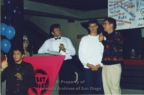 P001.328m.r.t Date Auction: man in white shirt and bowtie, man in white sweater and man in patterend sweater onstage
