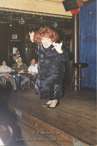 P001.261m.r.t Through The Years Fundraiser:drag queen wearing a black dress and red wig