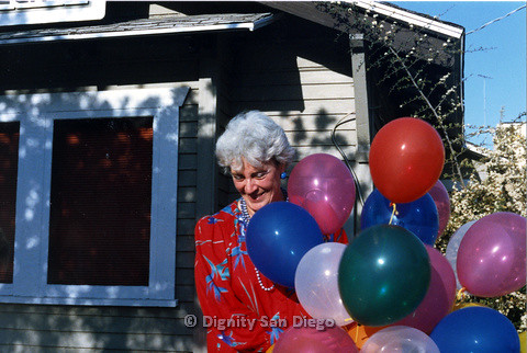 P103.178m.r.t San Diego Dignity Center: Woman with balloons in front of Center