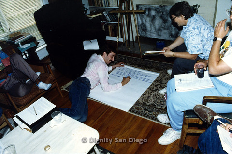 "P103.074m.r.t Dignity San Diego: Group of people surrounding man writing on big paper while lying on ground, paper titled ""AIDS & [illegible] Ministry"""