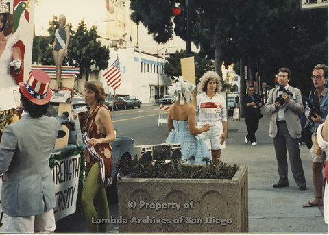 P024.127m.r.t Myth California Protest, San Diego, June 1986: two women at the center, the one on the left in a blue dress and dollar bills in her hair, the one on the right with a Campbell's Soup logo on her shirt and a wig