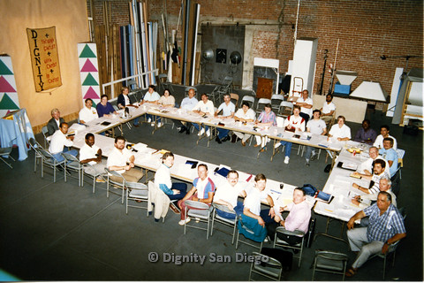 "P103.092m.r.t Dignity San Diego: Large group of people sitting around a long table. Sign on left ""Dignity + through Christ + with Christ + in Christ"""