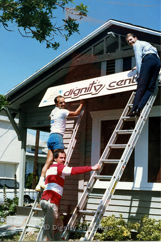P103.163m.r.t San Diego Dignity Center: Bruce Neveu (on right) and unidentified man hanging sign at front of Center with others stabilizing ladders from below