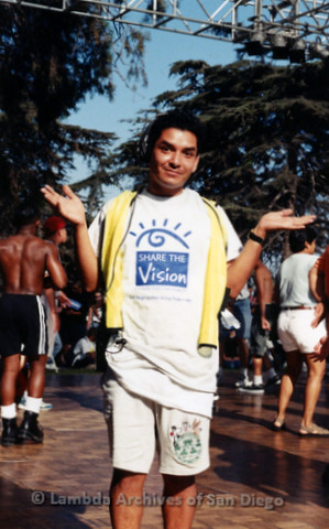 """P119.069m.r.t San Diego Pride 1997: A man wearing a fluorescent safety vest and """"Share the Vision"""" t-shirt"""