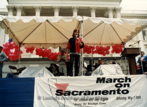 P019.161m.r.t March on Sacramento 1988 / Pre Parade gathering: Woman on stage speaking into microphone
