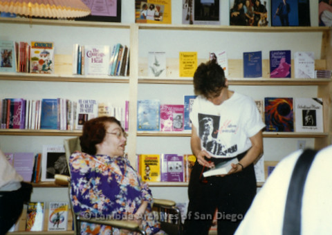 P169.069m.r.t Paradigm Women's Bookstore Grand Opening: Woman sitting in chair, woman standing with paperback book in bookstore