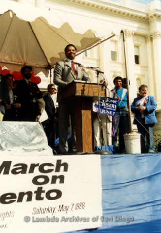 P019.125m.r.t March on Sacramento 1988 / Pre Parade gathering: Jesse Jackson speaking on stage in front of City Hall