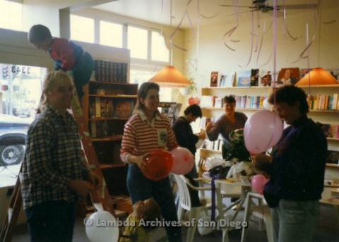 P169.077m.r.t Paradigm Women's Bookstore Grand Opening: Women decorating bookstore with balloons and child on ladder background
