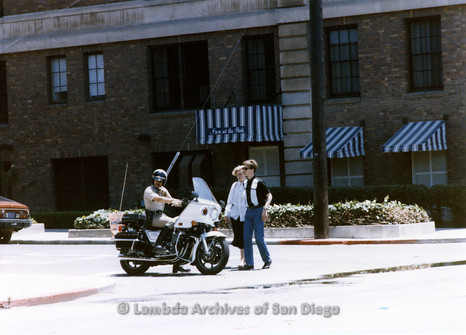 San Diego Lambda Pride Parade: Motorcycle Police officer waits at crosswalk while Parade Crowd Cross the Street.
