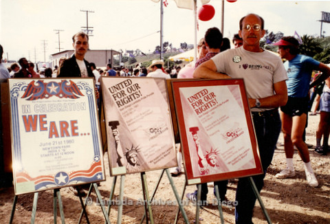 San Diego LGBT Center: Jess Jessop standing next to framed posters from the Pride collection, n.d.