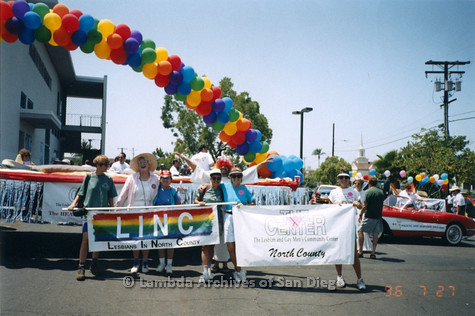 "P234.023m.r.t SD Pride Parade 1996: People holding banners: ""LINC Lesbians of North County"" and ""The Center North County"" with rainbow balloon arch in background"