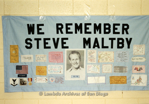 """P019.055m.r.t AIDS Quilt at San Diego Golden Hall 1988: Light blue quilt with snippets of writing and Navy memorabilia saying """"We remember Steve Maltby"""""""