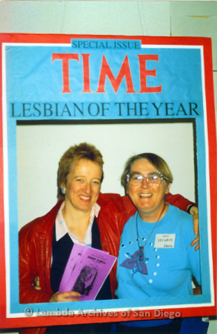 "Judy Fjell - Lesbian Performer (left) and Sheila Clark (right) at a Shirtails Dance standing behind a poster made to look like a ""Special Issue Time Lesbian of the Year"" magazine cover"