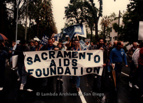 """P019.388m.r.t March on Sacramento 1988: People marching while holding banner that reads: """"SACRAMENTO AIDS FOUNDATION"""""""
