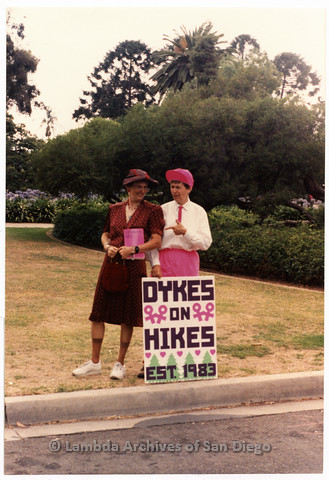 "P201.038m.r.t San Diego Pride Parade 1991: Karen Merry and Diane Germain standing behind sign that reads: ""Dykes on Hikes est. 1983"""