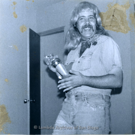 P355.071m.r.t MCC Oceanside Benefit 1976: Man wearing a wig holding a trophy