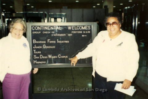 """""""The Magic Music Makes"""" San Diego Women's Chorus (SDWC) first choral festival with Sister Singers 1991: Cynthia Lawrence Wallace (right) and Peggy Heathers (left) posing in front of a welcome sign at airport"""