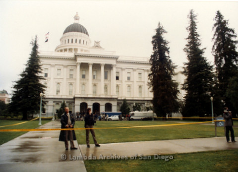 P019.164m.r.t March on Sacramento 1988 / Pre Parade gathering: Sacramento City Hall with two police officers standing behind yellow caution tape