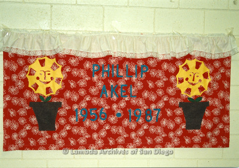 P019.057m.r.t AIDS Quilt at San Diego Golden Hall 1988: Red quilt with  smiling sun flowers dedicated to Phillip Akel