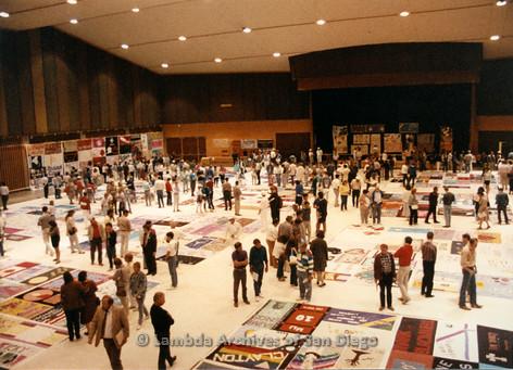 P019.199m.r.t AIDS Quilt at San Diego Golden Hall 1988: Crowd of visitors walking around AIDS Quilt exhibit