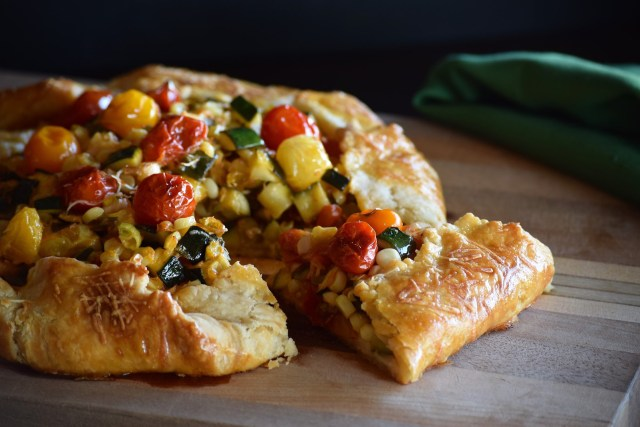a slice of burst tomato galette with corn and zucchini