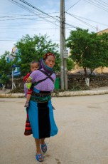 A Hmong Woman with a child on her back