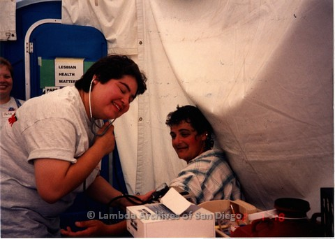 1992 - San Diego LGBT Pride Festival, Lesbian Health  Faire booth, sponsored by Womancare Feminist Health Clinic and The Lesbian Health Project of The San Diego LGBT Community Center. Maria Casas (left) volunteer and Womancare health advisor checks Nancy