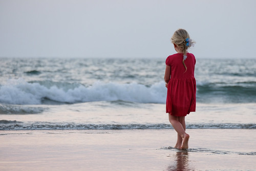 Beautiful Blonde Little Girl Dressed in a Red Dress Playing on the Beach
