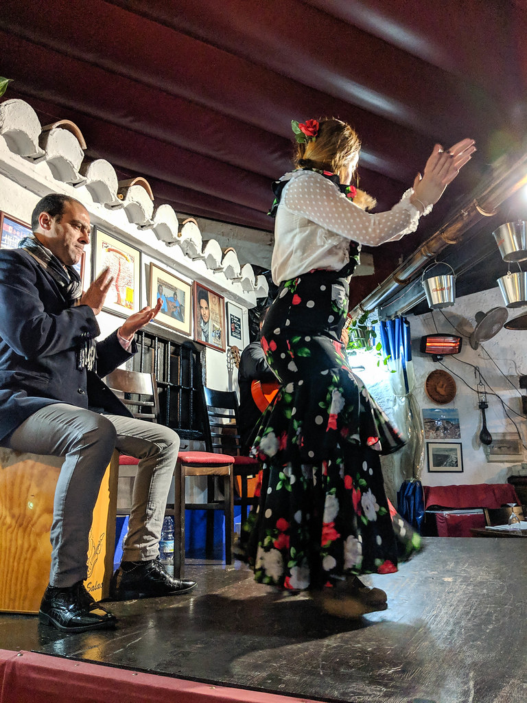 A woman dancing flamenco on the stage of a restaurant
