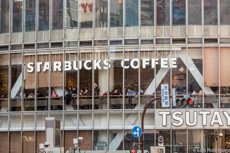 Gente tomando un café en el Starbucks y disfrutando de las vistas del cruce de Shibuya