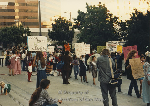P024.120m.r.t Myth California Protest, San Diego, June 1986: line of people holding signs, person in front holding a sign (Meat Markets Feed the Butchers)
