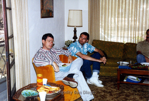P103.150m.r.t Three men seated in living room, one with a slice of watermelon