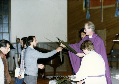 P103.036m.r.t Dignity San Diego, Palm Sunday: Male religious leader handing a palm leaf to a man