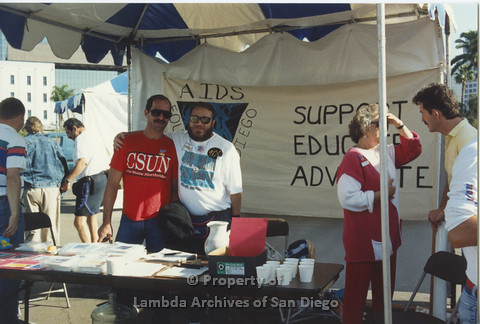 P001.124m.r.t AIDS Walk 1991: AIDS Foundation San Diego Booth with a banner (AIDS Foundation San Diego: Support, Educate, Advocate) 3 volunteers in booth
