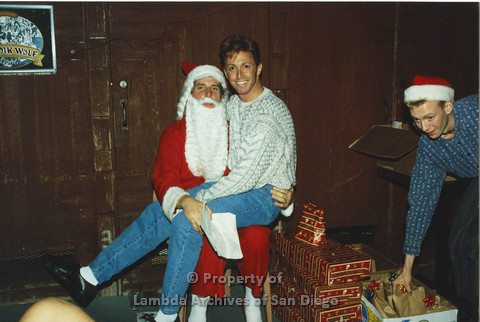 P001.294m.r.t X-mas: man in white patterned sweater sitting on Santa's Lap, man in blue sweater reaching for a gift