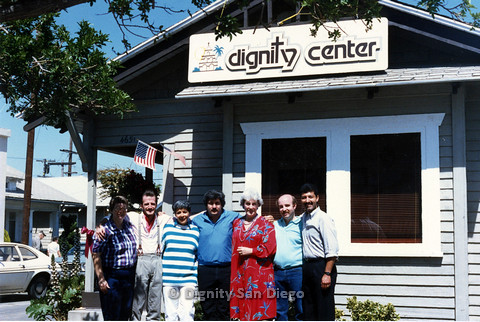 P103.168m.r.t Dignity Center: Seven people standing in front of Center. (Lucy at left, Henry Ramirez at right)