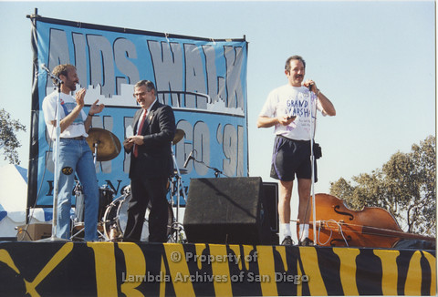 P001.128m.r.t AIDS Walk 1991: 3 people standing on stage, man speaking is wearing a t-shirt that says Grand Marshal