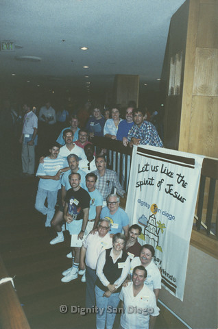P103.112m.r.t Dignity Ninth Biennial Convention 1989: Members posing in front of Dignity San Diego banner. Stan Lewis (white polo with hanging sunglasses), Bruce Neveu (Joker shirt) Pat McArron and Lucy at front