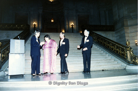 P103.128m.r.t Dignity Ninth Biennial Convention, San Francisco, 1989: Four people in formal attire standing and walking at base of staircase