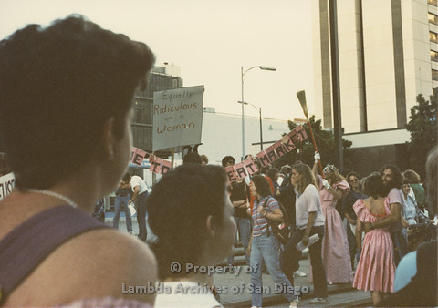 "P024.102m.r.t Myth California Protest, San Diego, June 1986: Sign attached to broom (""Welcome to the Meat Market""), sign in front (""Equally Ridiculous on a Woman"")"