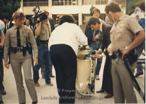 P024.131m.r.t Myth California Protest, San Diego, June 1986: people cleaning up a broken mirror and two police officers standing in front staring at the clean up
