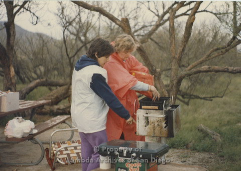 P024.058m.r.t Cathy Moore's 34th Birthday, Halley's Comet Weekend, Anza Borrego Desert 1986: 2 women working with a BBQ in the rain.