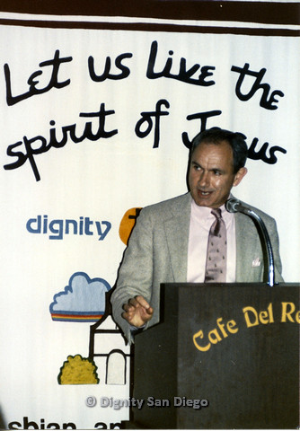 "P103.205m.r.t Dignity San Diego: Man in grey suit jacket talking on podium ""Café del Rey Moro"""