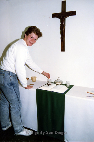 P103.185m.r.t Dignity San Diego: Woman standing in front of bible and cross, lighting a candle