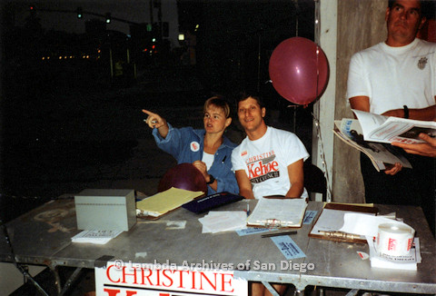 P151.047m.r.t  A man and a woman sitting outside at a campaign table