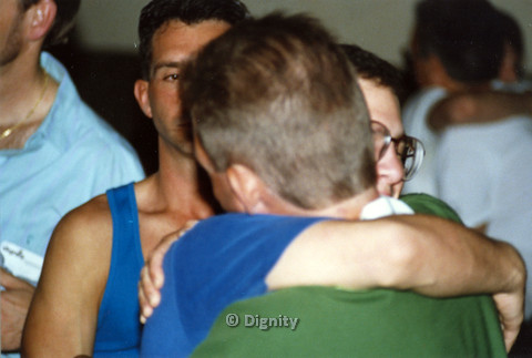 P104.177m.r.t Dignity San Diego: Two people hugging each other while standing in group.
