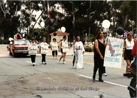 "P024.420m.r.t 1990 San Diego Pride parade: (L to R) unknown woman, Judy Bennett, Ellie Rapp, and Kithy Gately marching in front of truck with signs advertising a Beautiful Lesbian Thespians (BLT) production, ""Sisters"""